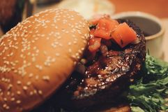 Закройте вверх домодельных томатов гамбургера говядины на верхней части Стоковые Изображения RF