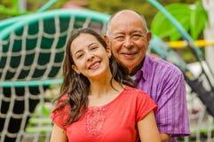 Закройте вверх дочери и отца обнимая один другого с влюбленностью на outdoors в парке Стоковая Фотография