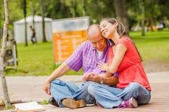Закройте вверх дочери обнимая его отца с влюбленностью на outdoors в парке Стоковые Изображения RF
