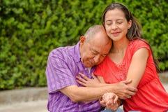 Закройте вверх дочери обнимая его отца с влюбленностью на outdoors в парке Стоковое Изображение RF