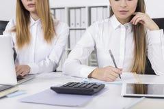 Закройте вверх 2 девушек работая в офисе Стоковое Изображение
