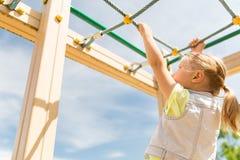Закройте вверх девушки взбираясь на спортивной площадке детей Стоковое Изображение