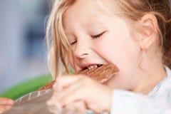 Закройте вверх девушки есть бар шоколада Стоковая Фотография RF