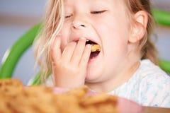 Закройте вверх девушки есть печенье обломока шоколада Стоковые Изображения