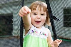 Закройте вверх девушки малыша на ее батуте Стоковое Изображение