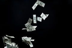 Закройте вверх денег доллара США летая над чернотой Стоковая Фотография