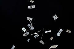 Закройте вверх денег доллара США летая над чернотой Стоковые Изображения RF