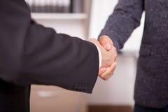 Закройте вверх 2 деловых партнеров тряся руки в офисе Стоковое фото RF