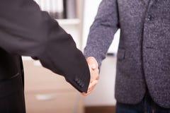 Закройте вверх 2 деловых партнеров тряся руки в офисе Стоковая Фотография RF