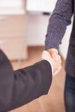 Закройте вверх 2 деловых партнеров тряся руки в офисе Стоковые Фото