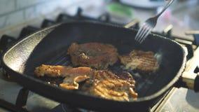 Закройте вверх жарить мясо на гриле в 4K акции видеоматериалы