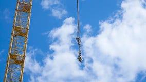 Закройте вверх желтого и зеленого заграждения крана с главными блоком и кливером против ясного голубого неба Краны здания башни акции видеоматериалы