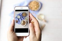 Закройте вверх женских рук держа мобильный телефон фотографируя хлопья granola, югурт молока и br вегетарианца смешивания следа d Стоковое фото RF