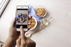 Закройте вверх женских рук держа мобильный телефон фотографируя хлопья granola, югурт молока и br вегетарианца смешивания следа d Стоковые Фотографии RF