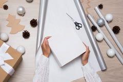 Закройте вверх женских рук пакуя подарки рождества стоковое фото rf