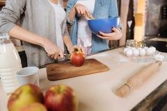 Закройте вверх женских рук пока режущ яблоко Стоковая Фотография RF