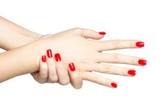 Закройте вверх женских рук с красным маникюром Стоковые Изображения