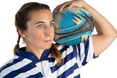 Закройте вверх женского игрока держа шарик рэгби пока смотрящ прочь Стоковые Изображения