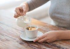 Закройте вверх женского лить молока в кофе стоковое фото