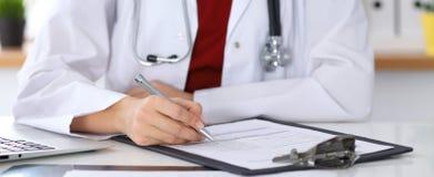 Закройте вверх женского доктора заполняя вверх по форме для заявления пока сидящ на таблице Стоковые Изображения RF