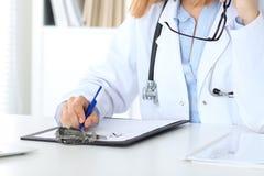Закройте вверх женского доктора писать медицинский рецепт, как раз руки Стоковое Фото