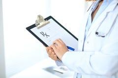 Закройте вверх женского доктора писать медицинский рецепт на доске сзажимом для бумаги пока стоящ Стоковые Фото