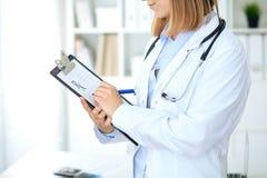 Закройте вверх женского доктора писать медицинский рецепт на доске сзажимом для бумаги пока стоящ Стоковая Фотография