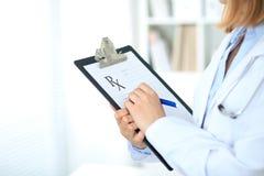 Закройте вверх женского доктора писать медицинский рецепт на доске сзажимом для бумаги пока стоящ Стоковая Фотография RF