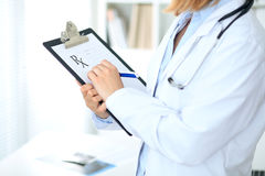 Закройте вверх женского доктора писать медицинский рецепт на доске сзажимом для бумаги пока стоящ Стоковые Изображения