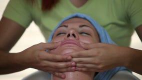 Закройте вверх женского терапевта массажируя кожу ухода за лицом клиентов видеоматериал