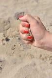 Закройте вверх женской руки выпуская песок Песок пропуская через Стоковое Изображение