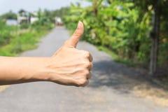 Закройте вверх женской руки показывая большие пальцы руки вверх по знаку против на улицы Стоковые Изображения RF