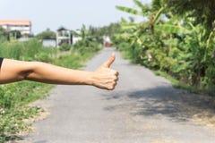 Закройте вверх женской руки показывая большие пальцы руки вверх по знаку против на улицы Стоковое Фото