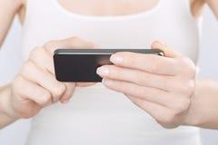 Закройте вверх женщины в белизне используя smartphone Стоковые Изображения