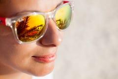 Закройте вверх женщины в солнечных очках с отражением пляжа Стоковое Изображение