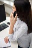 Закройте вверх женщины говоря на smartphone на офисе Стоковые Изображения RF