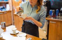 Закройте вверх женщины делая кофе на магазине или кафе Стоковые Фотографии RF