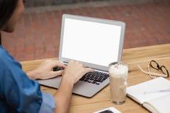 Закройте вверх женщины используя компьтер-книжку пока сидящ на таблице Стоковое фото RF
