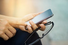 Закройте вверх женщины используя передвижной умный телефон внешний и стекла Стоковая Фотография RF