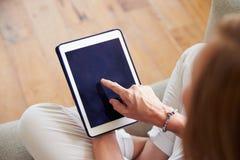 Закройте вверх женщины используя таблетку цифров дома Стоковое Фото