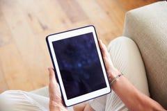 Закройте вверх женщины используя таблетку цифров дома Стоковые Фото