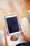 Закройте вверх женщины используя таблетку цифров дома Стоковое Изображение RF