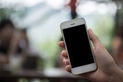 Закройте вверх женщины используя умный телефон с пустыми чернью и чашкой Стоковое Изображение