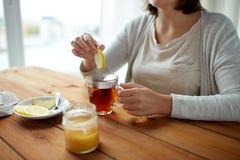 Закройте вверх женщины добавляя лимон к чашке чая стоковые изображения rf
