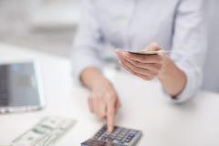 Закройте вверх женщины подсчитывая деньги с калькулятором Стоковая Фотография