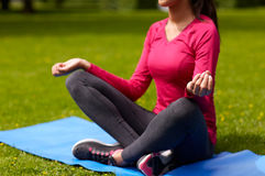 Закройте вверх женщины размышляя на циновке outdoors Стоковое Фото