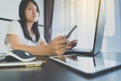 Закройте вверх женщины руки держа мобильный телефон с ручкой и используя компьтер-книжку для онлайн концепции покупок Стоковые Изображения RF