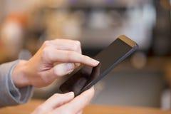 Закройте вверх женщины рук используя ее сотовый телефон в re Стоковое фото RF