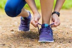 Закройте вверх женщины связывая шнурки ботинка в разминке лета Стоковые Фотографии RF
