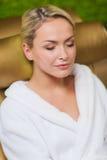 Закройте вверх женщины сидя в робе ванны на курорте Стоковые Фото